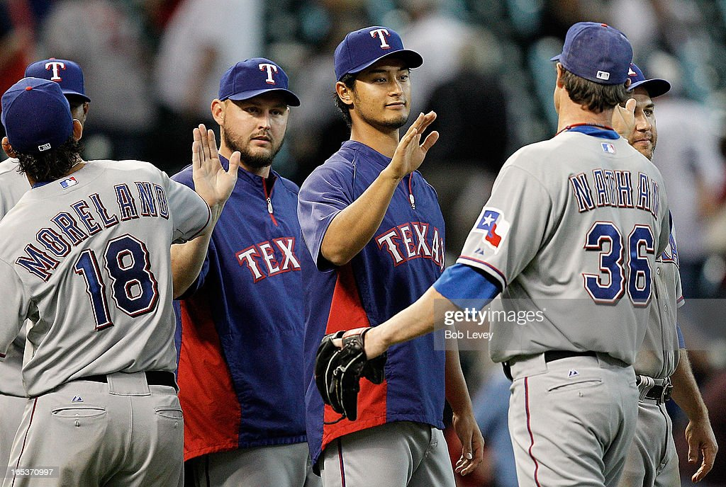 Yu Darvish #11 high-fives teammate Joe Nathan #36 of the Texas Rangers after defeating the Houston Astros 4-0 at Minute Maid Park on April 3, 2013 in Houston, Texas.