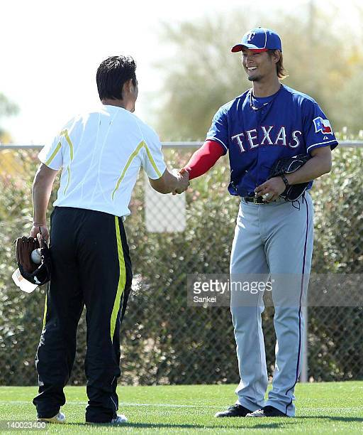 Yu Darvish of Texas Rangers shakes hands with former MLB player Akinori Otsuka during the Texas Rangers spting training at Surprise Stadium on...
