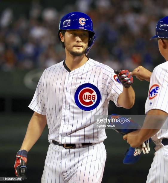 Yu Darvish of the Chicago Cubs and the first base coach fist bump after hitting an RBI single during the second inning of the game against the San...
