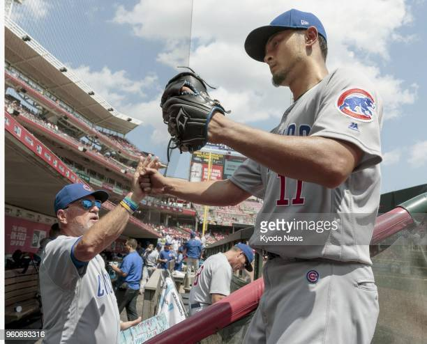 Yu Darvish of the Chicago Cubs gives highfive to manager Joe Maddon after finishing the fifth inning against the Cincinnati Reds in Cincinnati Ohio...