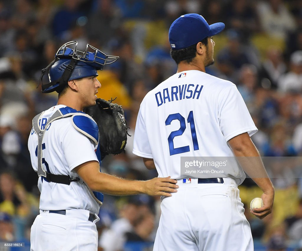 Yu Darvish #21 of the Los Angeles Dodgers gets some encouragement from Austin Barnes #15 of the Los Angeles Dodgers in the fifth inning of the game against the Chicago White Sox at Dodger Stadium on August 16, 2017 in Los Angeles, California.
