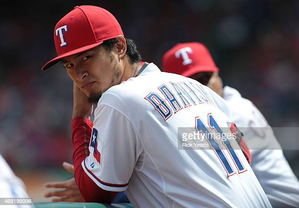 Yu Darvish of the Texas Rangers looks on from the dugout in the second inning of the Rangers home opener against the Houston Astros at Globe Life...