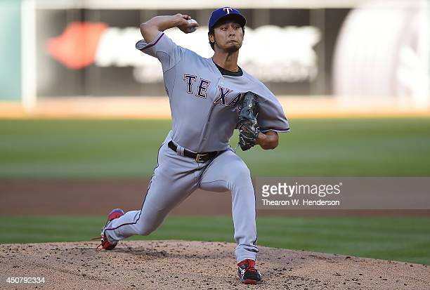 Yu Darvish of the Texas Rangers pitches in the bottom of the first inning against the Oakland Athletics at Oco Coliseum on June 17 2014 in Oakland...
