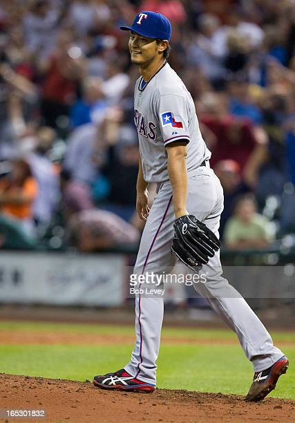 Yu Darvish of the Texas Rangers reacts after not being able to field a line drive back through his legs in the ninth inning by Marwin Gonzalez of the...