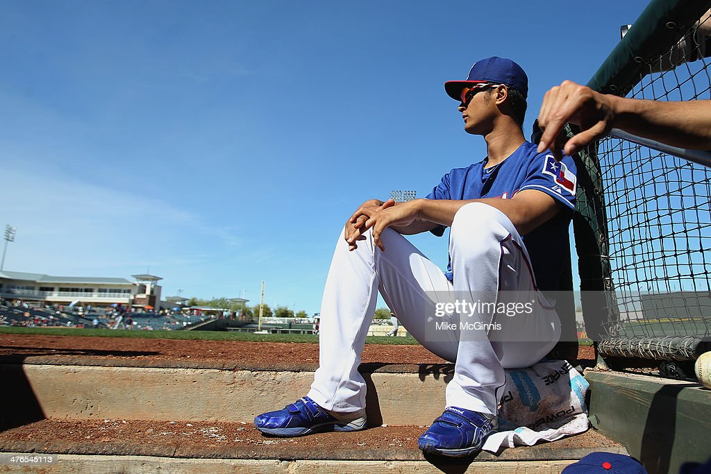 Yu Darvish #11 of the Texas Rangers sits on the edge of the dugout during the top of the fourth inning against the Cleveland Indians at Surprise Stadium on March 03, 2014 in Surprise, Arizona.
