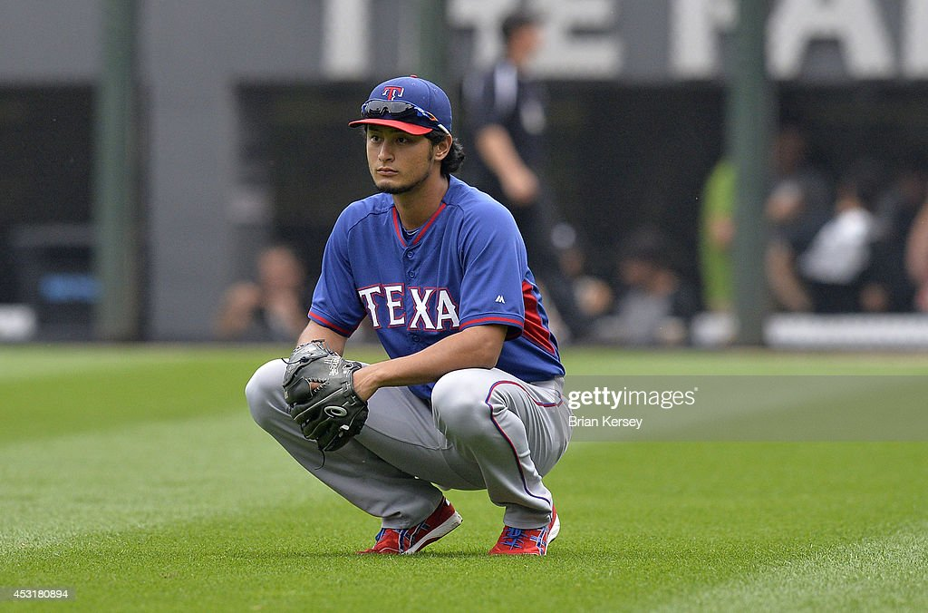Yu Darvish #11 of the Texas Rangers squats in the outfield during batting practice before the game against the Chicago White Sox at U.S. Cellular Field on August 4, 2014 in Chicago, Illinois.