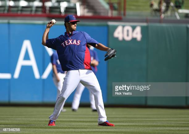 Yu Darvish of the Texas Rangers throws the ball back to home during batting practice before the start of the game against the Oakland Athletics at...