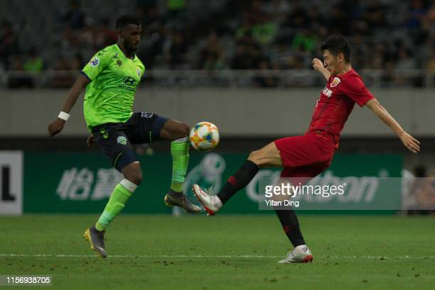 Yu Hai of Shanghai SIPG and Bernie IbiniIsei of Jeonbuk Hyundai Motors compete for the ball during the AFC Champions League round of 16 first leg...