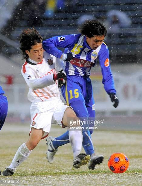 Yu Hasegawa of Montedio Yamagata and Naoshi Nakamura of Nagoya Grampus compete for the ball during the JLeague match between Montedio Yamagata and...