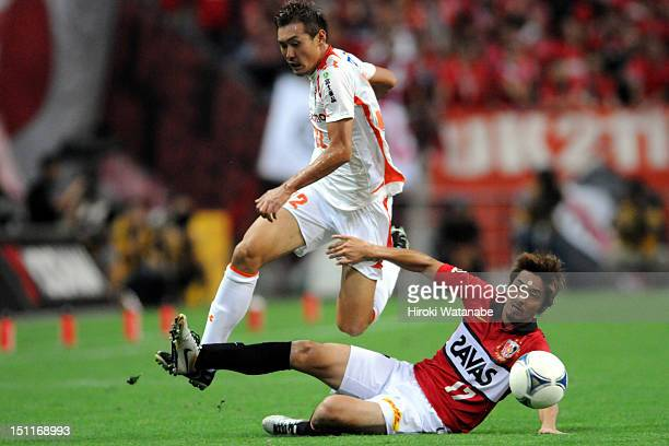 Yu Hasegawa of Omiya Ardija is tackled by Mitsuru Nagata of Urawa Red Diamonds during the J.League match between Urawa Red Diamonds and Omiya Ardija...
