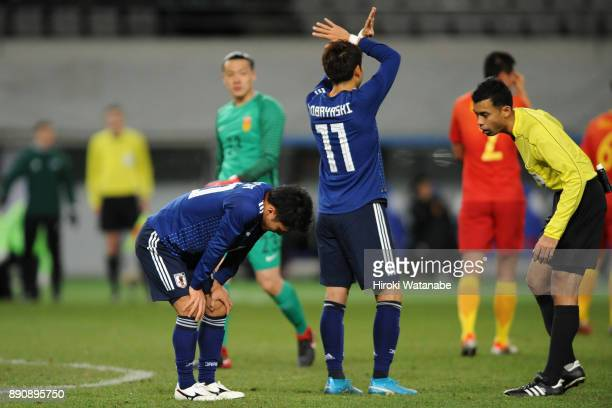 Yu Kobayashi of Japan sends a sign to the bench as Ryota Oshima is injured during the EAFF E1 Men's Football Championship between Japan and China at...