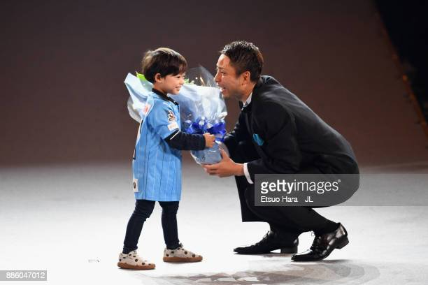 Yu Kobayashi of Kawasaki Frontale celebrates the JLeague Player of the Year Award with his child during the 2017 JLeague Awards at Yokohama Arena on...