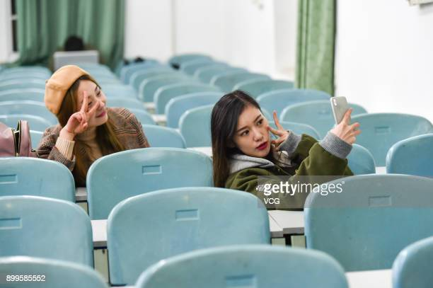 Yu Linghan takes selfies with her schoolmate Fan Chuanyang at classroom on December 23 2017 in Chengdu Sichuan Province of China 20yearold Chinese...