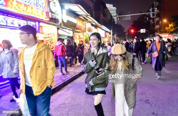 Yu Linghan walks at a food street outside the University of Electronic Science and Technology of China on December 23 2017 in Chengdu Sichuan...