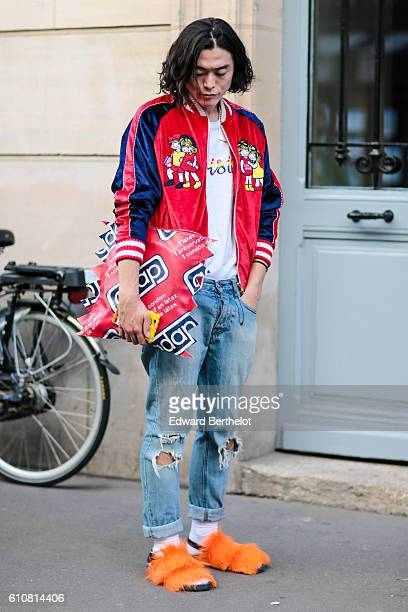 Yu Masui is wearing a red and blue bombers jacket and a clutch as an imitation of a Durex condom outside the Paskal show during Paris Fashion Week...