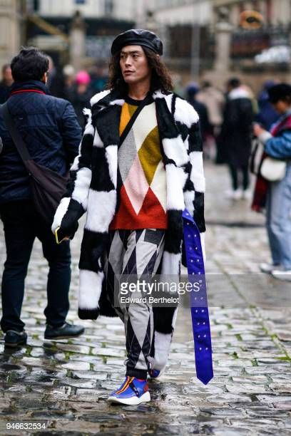 Yu Masui wears a beret hat a black and white checked coat black and white checked pants a colored pull over outside Thom Browne during Paris Fashion...