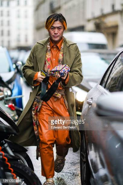Yu Masui wears a green/khaki coat, a brown/orange leather shirt, pants, a colored clutch, during Paris Fashion Week - Womenswear Fall/Winter...