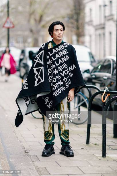 Yu Masui wears earrings a black poncho with white inscriptions white green and golden color scarf design pants black studded sneakers during London...