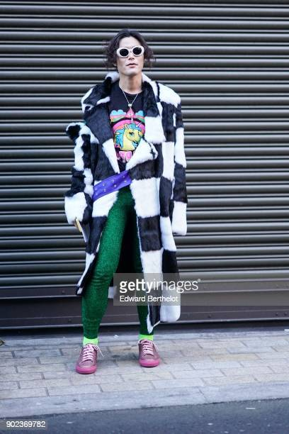 Yu Masui wears sunglasses a checked black and white coat green pants during London Fashion Week Men's January 2018 at on January 7 2018 in London...