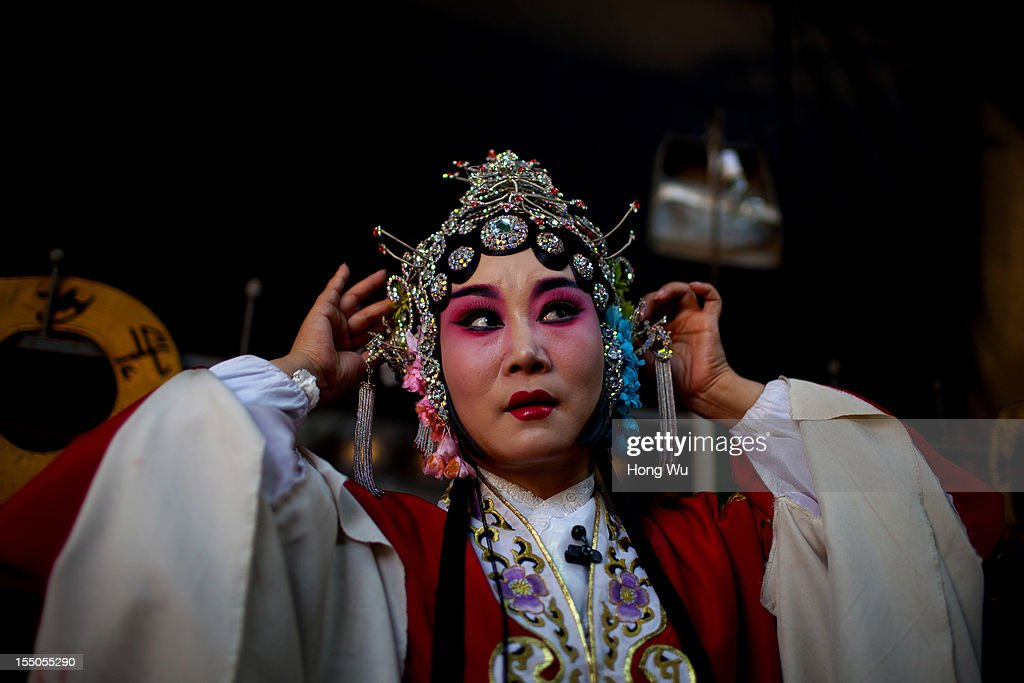 A Yu Opera performer Shi Ru, prepares to perform on October 30, 2012 in Zhengzhou, China. As many as 60 performers from the Sanmenxia theatrical troupe are invited to perform Chinese traditional Yu Opera for local villagers in rural Zhengzhou city to celebrate the village's temple fair and earn 10,000 RMB yuan (US$ 1,600) each performance. Yu Opera, also called Henan Bangzi or Ou Opera, is one of the most popular local operas in China. Its earliest written record can be traced back more than 200 years and at the end of the Qing Dynasty (A.D. 1644-1911), the opera became widespread across the Henan province. After the establishment of the People's Republic of China in 1949, it experienced rapid growth not only in the villages and cities of Henan Province but also throughout the country. In recent years its popularity has declined due to young people's attraction to more modern cultures.