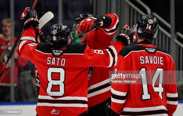 Yu Sato, Thomas Caron and Nicolas Savoie of the Quebec Remparts celebrate their victory against the Shawinigan Cataractes during their QMJHL hockey...
