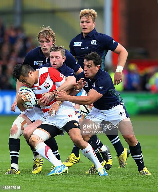 Yu Tamura of Japan is held up by the Scotland defence during the 2015 Rugby World Cup Pool B match between Scotland and Japan at Kingsholm Stadium on...