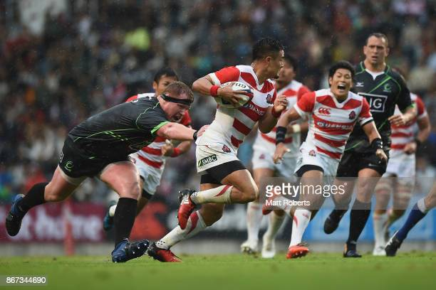 Yu Tamura of Japan XV takes on the defence of Jacques Van Rooyen of World XV during the international match between Japan XV and World XV at Level...