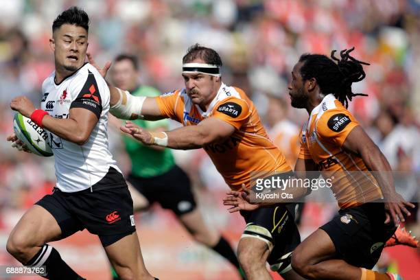 Yu Tamura of the Sunwolves makes a break against Francois Uys and Sergeal Petersen of the Cheetahs during the Super Rugby Rd 14 match between...