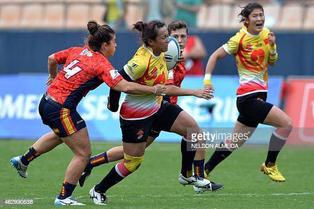 Yu Xiaoming of China runs past a tackle from from Patricia Garcia of Spain during their quarter final match of the IRB Women's Sevens World Series in...
