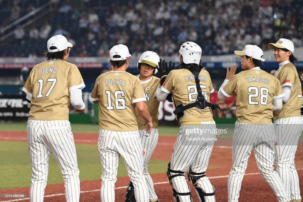 Yu Yamamoto #5 (C) of Japan celebrates after hitting a grand slam in the second inning against Puerto Rico during their Playoff Round at ZOZO Marine Stadium on day nine of the WBSC Women's Softball World Championship on August 10, 2018 in Chiba, Japan.