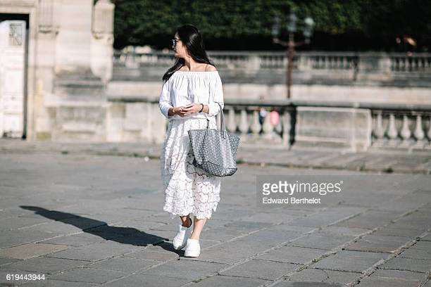 Yuan Tao is wearing a Maje white dress Maison Margiela white shoes a Zara white top Dior sunglasses and a Goyard gray bag on October 31 2016 in Paris...