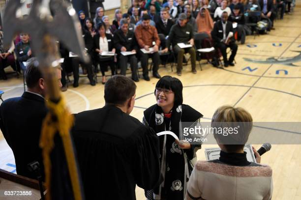 Yuanhao Chuge formerly of China accepts her certificate of citizenship from Immigration Judge Ivan Gardzelewski after taking the Oath of Allegiance...