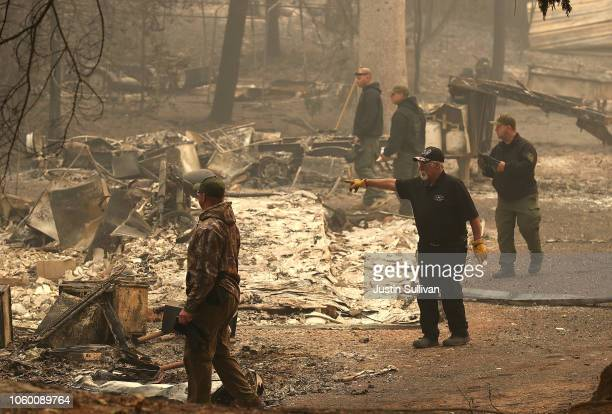 Yuba and Butte County sherriff deputies search a destroyed home for a reported victim of the Camp Fire on November 10 2018 in Paradise California...