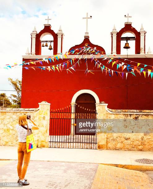 yucatan, mexico: female tourist taking photo of beautiful red church - merida mexico stock photos and pictures