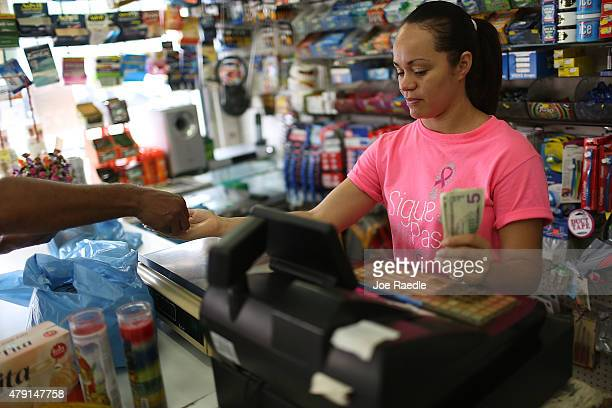 Yudelkis Hernandez rings up a sale on July 1 2015 in San Juan Puerto Rico The island's residents are dealing with increasing economic hardships and a...