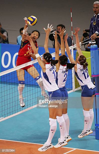 Yuehong Zhang of China sends a shot past Ekaterina Gamova Irina Tebenikhina and Marina Sheshenina of Russia in the women's indoor Volleyball gold...