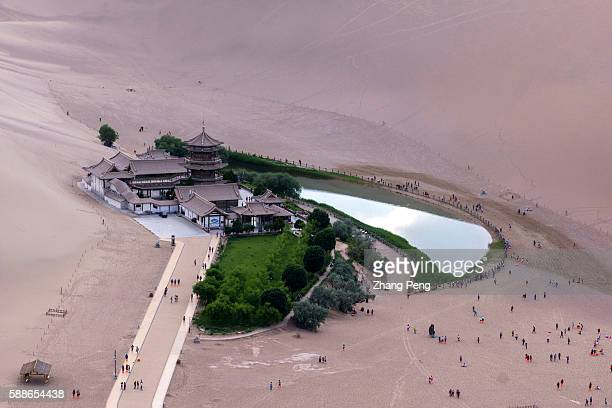 Yueyaquan a crescentshaped lake in an oasis surrounded by the EchoingSand Mountain is a popular travel destination as a natural wonder in the Gobi...