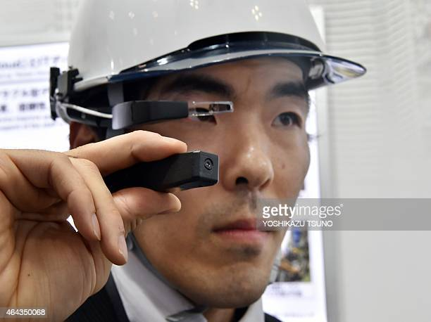 Yugo Morimoto an employee at Japan's hightech firm Hitachi displays a newly developed wearable device for factory workers at the International Smart...