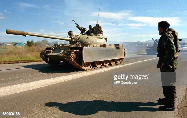 A Yugoslav Army soldier watches a convoy of 16 tanks rolling pass on a street near Pristina 29 October 1998 on the way back to their barracks in the...