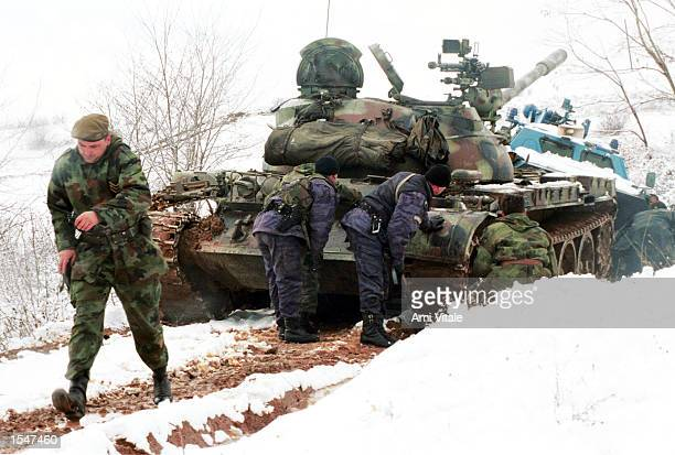 Yugoslav Army soldiers hide behind their tank as Kosovo Liberation Army soldiers launch mortars in the village of Bukos in Kosovo Tuesday February 23...