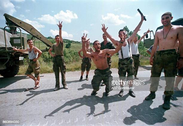 Yugoslav army soldiers joke with journalists while flashing the Serbian threefingered sign in Kursumlija the first Serbian town outside the Kosovo...
