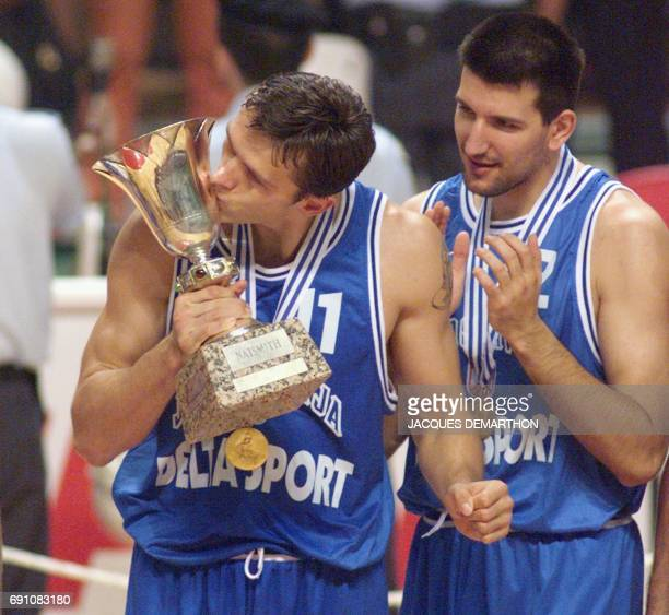 Yugoslavian center Zeljko Rebraca kisses the trophy as center Pedrag Drobnajk applauds on the podium 09 August in Athens after winning the thirteen...