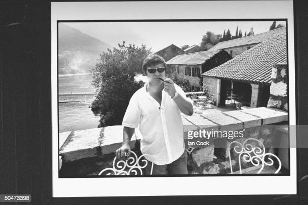 Yugoslavian chess promotor Jezdimir Vasiljevic smoking his pipe on balcony at Hotel Sveti Stefan where chess champion Bobby Fischer is busy...