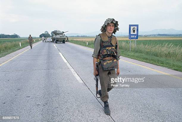 A Yugoslavian Federal Army soldier walks down a road during retreat due to an ambush by nongovernmental Slovenian troops The Slovenian and...