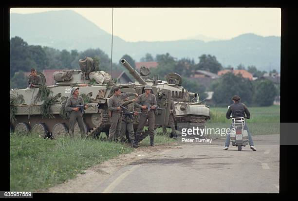 Yugoslavian Federal Army soldiers point guns in the direction of a civilian on a motor scooter