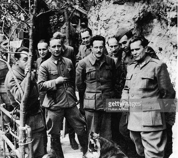 Yugoslavian leader Marshall Josip Broz Tito and his staff pose with Chetnik leader Dragoljub 'Drazha' Mihailovic at his secret mountain retreat...