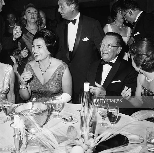 Yugoslavian President and Mrs. Tito are the happy center of attention October 24 as they attend the United Nations Day Ball at the Waldorf Astoria...