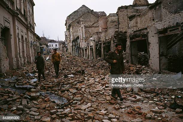 Yugoslavian soldiers and Serb paramilitaries including Zeljko Arkan Raznatovic walk past bombed buildings riddled with bullet holes and streets...