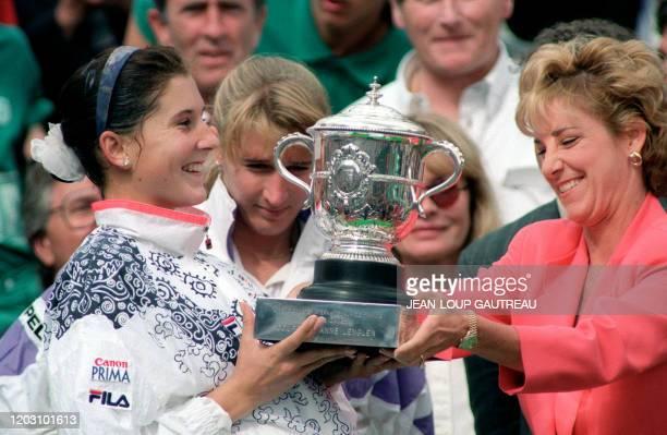 Yugoslavian tennis player Monica Seles receives the Winner's trophy from American former tennis star Chris Evert here 06 june 1992 at Roland Garros...