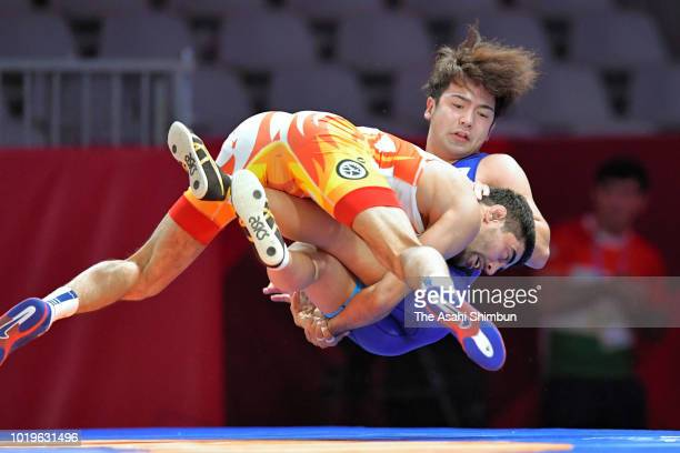 Yuhi Fujinami of Japan is tackled by Bekzod Abdurakhamonov of Uzbekistan in the Wrestling Men's Freestyle 74kg semifinal at the Jakarta Convention...